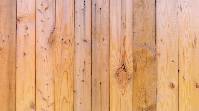 Plain fresh recycled wood background in panels, showing wood grain and nuts, with imperfections.  Copy space and slightly blurred background, with a rustic style. Wood has not been weathered.