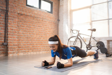 Cyclist Exercising with her plank pose in the house She uses a timer phone