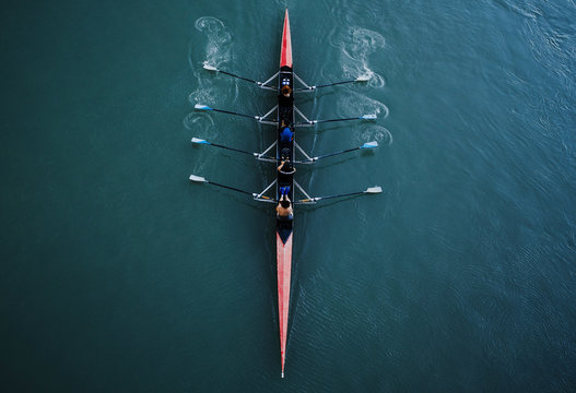 Kayak from above with 4 rowing people. Blue and aqua water background. Sport and moving concept. Red kayak and 8 paddles.