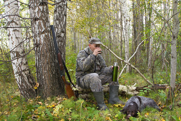 a hunter and his gundog rest while hunting