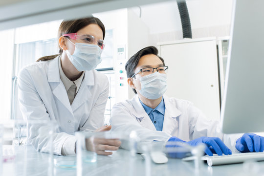 Two lab workers in masks, eyeglasses and whitecoats looking at computer screen