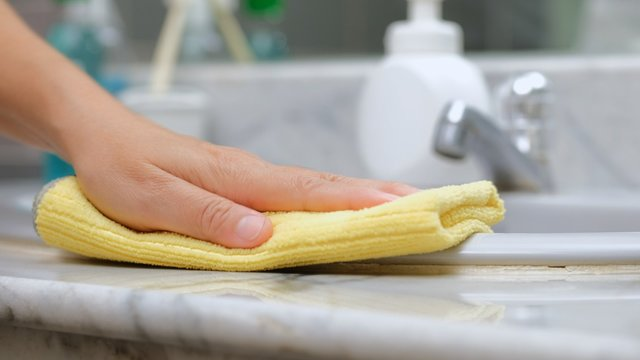 Close up of hands in bathroom wiping down surface with yellow cloth,prevention to coronavirus, hygiene  to stop spread of germs and bacteria .slow motion