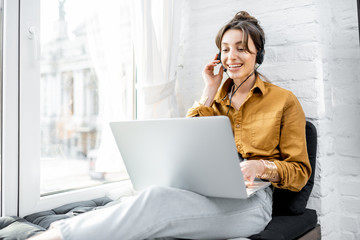 Young woman with a headset working online on computer while sitting on the window sill at home. Concept of studying or working from home online