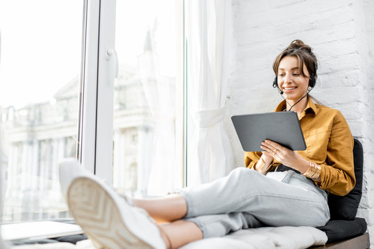 Young woman with a headset working online on a digital tablet while sitting on the window sill at home. Concept of studying or working from home online