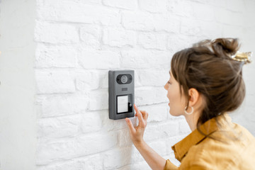Woman rings the house intercom with a camera installed on the white brick wall