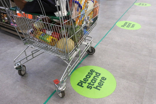 Social distancing marks on supermarket floor intended to stop or slow down the spread of a contagious Coronavirus (COVID-19)  disease.