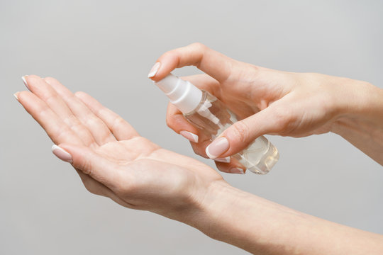 Female hands using hand sanitizer spray dispenser over light grey background