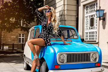 Polka dots fashion. Beautiful blonde young woman near the car. Spring and summer fashion model concept. Wall mural