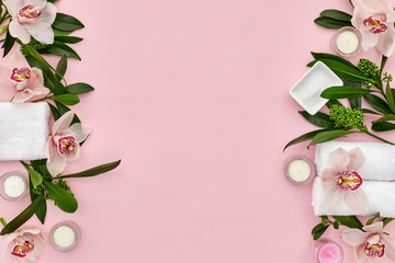 Photo sur Toile Roses wellness and spa composition with towels, candle, tropical leaves and orchid flowers on pink background. top view. copy space