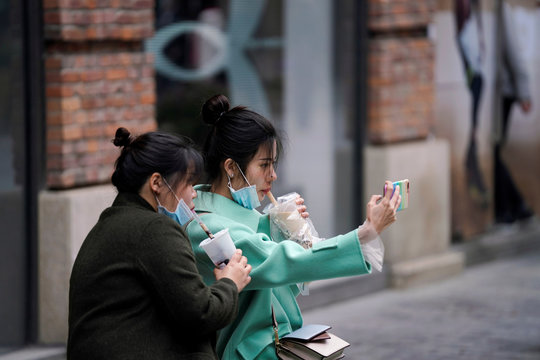 Women with face masks enjoy their bubble tea at a shopping complex in Wuhan