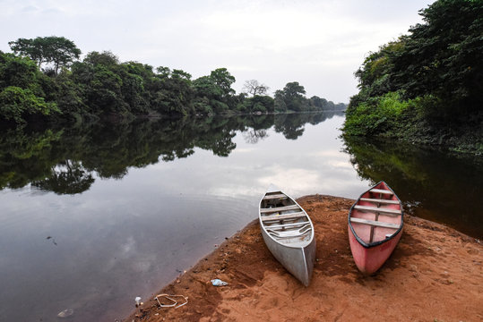 A pair of canoes are seen on the shore of a river in the Outamba-Kilimi national park