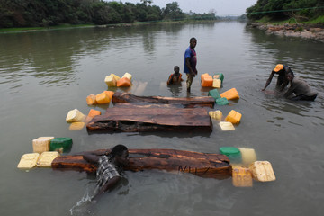 Men float rosewood logs across a river using empty jerrycans outside the town of Kamakwie