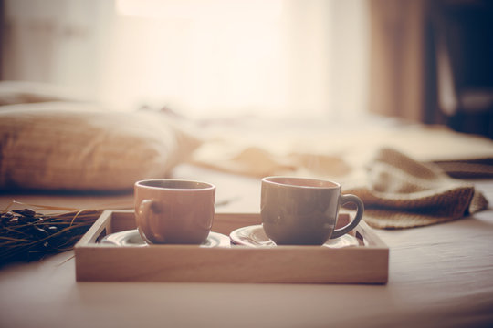 Two cups on bed.