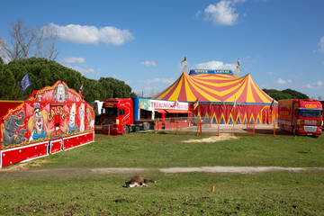 roger lanzac circus tent with red yellow stripes and blue sky