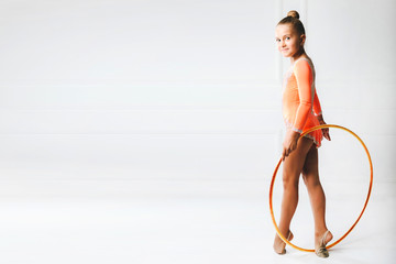 Beautiful fit gymnast girl in sportswear peach dress posing with athletic hoop standing, looking from behind