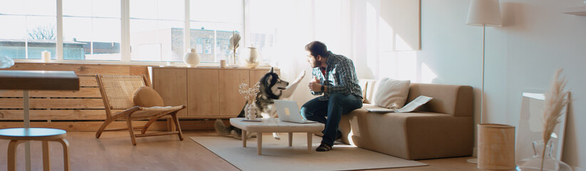 Middle Eastern male working from home, having a video call, dog sits near him. Stay home, quarantine remote work Wall mural