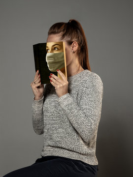 Happy world book day 2020, be safe and read to become someone else - woman covering face with book in mask while reading on grey studio background. Celebrating, education, art, protection concept.