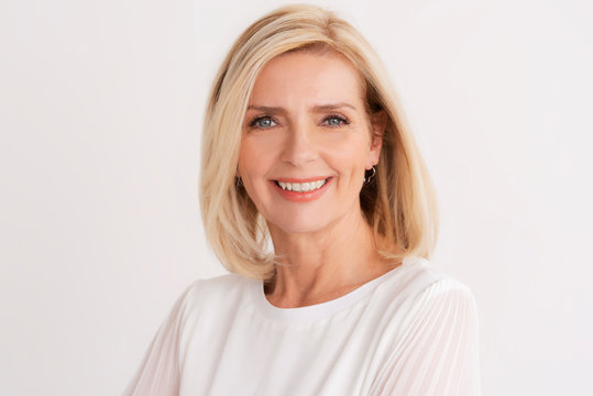 Headshot of blond senior woman while standing at isolated white background