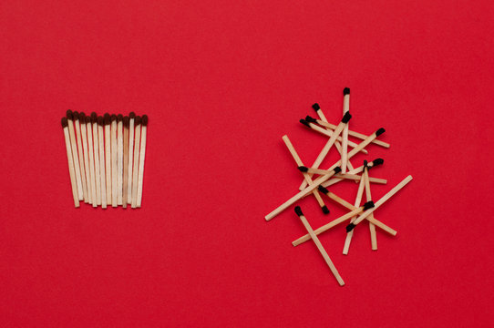 Used and unused matches on red background. Order and chaos, dead or  alive, healthy and sick, fresh and rotten, good and bad, free and captive, self-isolation, quarantine concept.