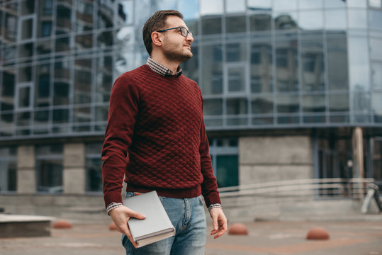 Portrait of a man in glasses for vision wearing a shirt and sweater, with , frame, with books, notebook in his hands, on the background of a modern building. Education, institute, business, outside