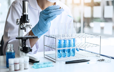 Biochemistry laboratory research, Scientist or medical in lab coat holding test tube with Using Microscope reagent with drop of color liquid over glass equipment working at the laboratory
