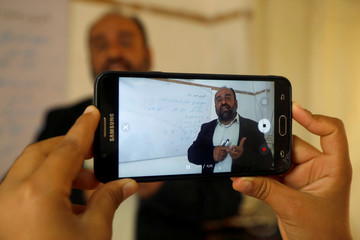 Palestinian Arabic language teacher is filmed by his daughter as he records an online class to his students, in the Israeli-occupied West Bank