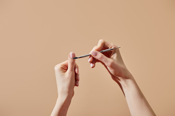 Poster Manicure Cropped view of woman doing manicure using cuticle pusher isolated on beige