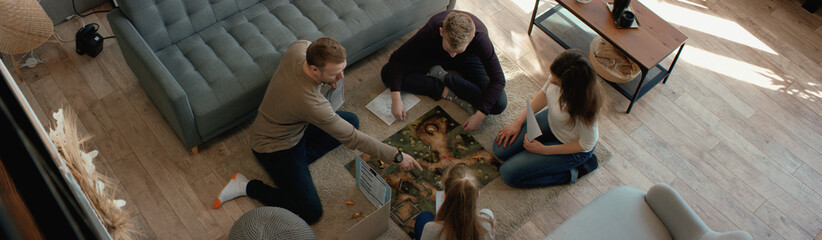 OVERHEAD Family - father, mother and two kids playing a board game together. Stay home, quarantine. Board game is custom made for the shot