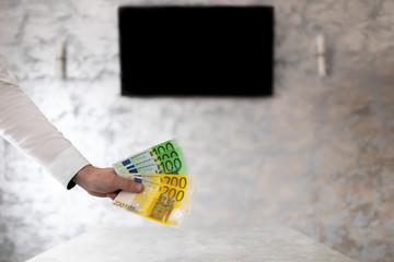 Fototapeta Biznesmen w biurze trzymający banknoty euro w dłoni obraz
