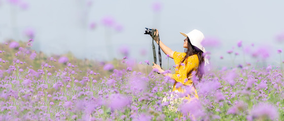 Traveler or tourism Asian women standing and holding camera take a photo flower in the purple  verbena field in vacations time.  People lifestyle freedom and relax spring meadow Fotomurales