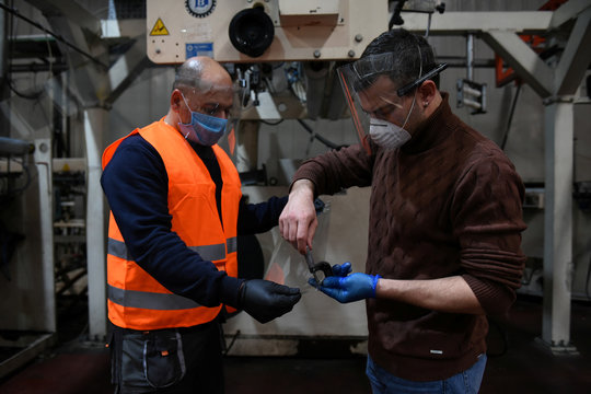 Product developer of Veltio startup company Theodoros Marioglou overlooks the production of face shields with a factory worker, following the outbreak of coronavirus disease (COVID-19) in Thessaloniki