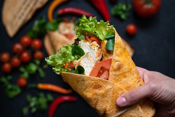 Mexican corn tortilla wrap with grilled chicken and fresh vegetables. Dietary healthy dish. Close-up female hand holding tortilla sandwich