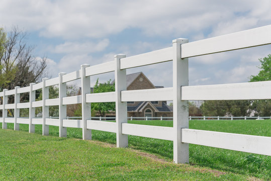 Shallow DOF long white fence with defocused farm house ranch in background in Ennis, Texas, USA