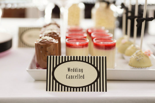 """Sweet table with """"Wedding Cancelled"""" card. Failing event industry concept."""