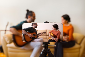 Guitar lessons tutorial with smart phone. Indoor screen shot of musical course. Technology and leisure. Professor teaching how to play an instrument. Video screen recording music online class at home. Fotobehang