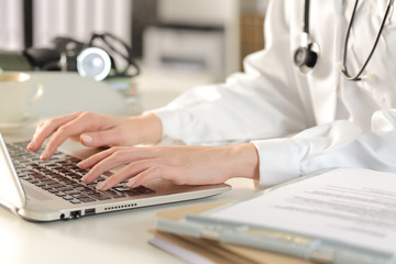 Doctor woman hands typing on laptop at the office