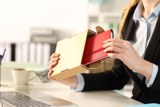Executive hands unboxing package with agenda at the office