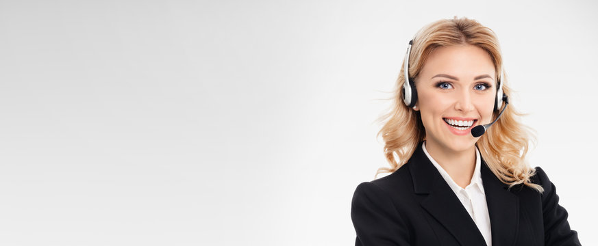 Portrait of happy smiling young support phone operator or confident businesswomen in headset, over grey background, with blank copy space area for slogan or text message.