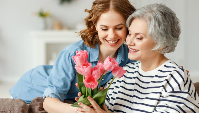 Young woman giving flowers to senior mother
