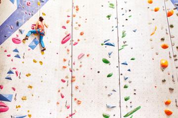 Woman rock climbing indoors.