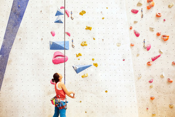 Woman getting ready for rock climbing indoors.
