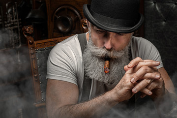 Old man smoking a cigar indoors. Mafia concept. Stylish male in his cabinet. Bearded man.