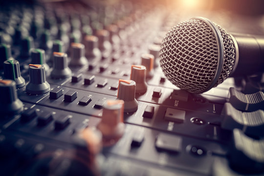 Sound recording studio mixing desk with microphone on mixer
