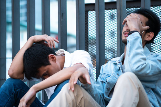 Two stress unemployed Asian men from world economics crisis, lay off people in Coronavirus or Covid-19 epidemic outbreak, young man sitting on floor depressed and sad getting fired, business problem