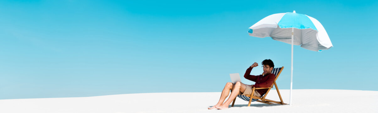 freelancer sitting with laptop in deck chair under umbrella on sandy beach against blue sky, panoramic shot