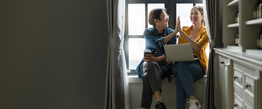 happiness asian couple male and female friend enjoy chat gossip together in coffee break asian froend use laptop smartphone casual meeting next to window home background