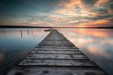 Magnificent long exposure lake sunset with boat and a wooden pier Wall mural