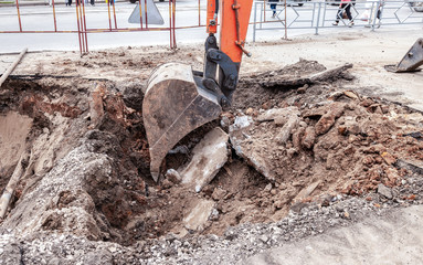 Construction works on rusty iron pipes at a depth of excavated trench
