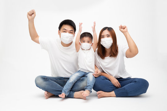 Asian family wearing protective medical mask for prevent virus Wuhan Covid-19 and hand up and sitting together on floor isolated white background. Family protection from contaminated air concept