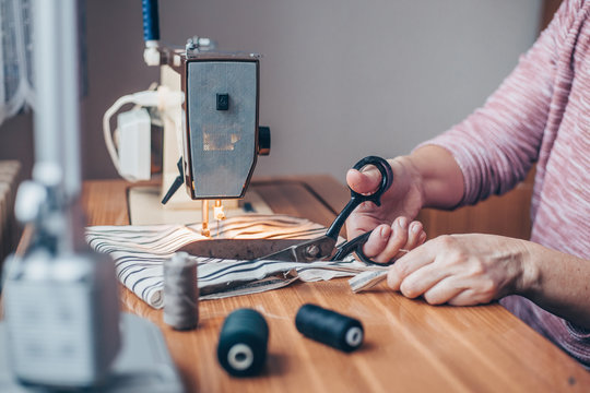 Woman sewing medical masks on sewing machine during coronavirus pandemic, protection against covid-2019, homemade sewing